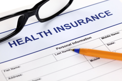 Health insurance claim form with glasses and ballpoint pen